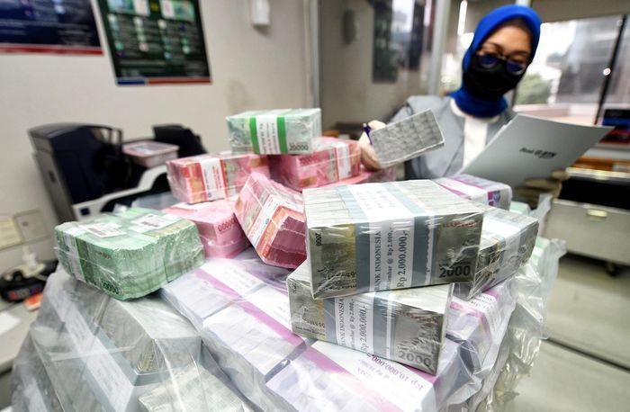 Seorang Petugas Teller PT Bank Tabungan Negara (Persero) Tbk. menghitung uang kertas di salah satu Kantor Cabang Bank BTN Jakarta Harmoni, di Jakarta, Senin (18/5). Foto: dok. Bank BTN