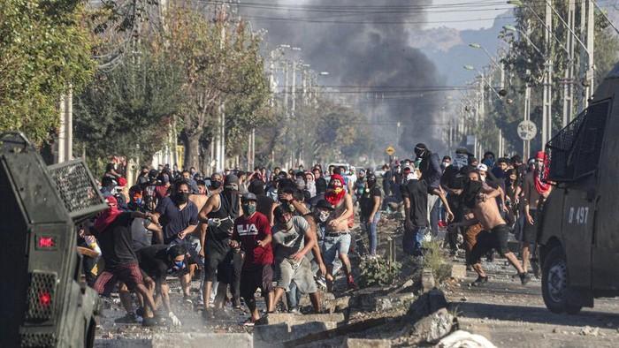 Demonstrasi berujung bentrok terjadi di Santiago, Chile. Warga yang menuntut bantuan makanan selama lockdown melempari polisi dengan batu.