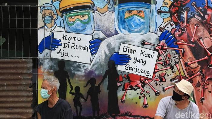 Sebuah mural mejeng di kawasan Jalan Kinayungan, Tangerang Selatan. Mural tersebut berisi pesan untuk bersama melawan Corona.