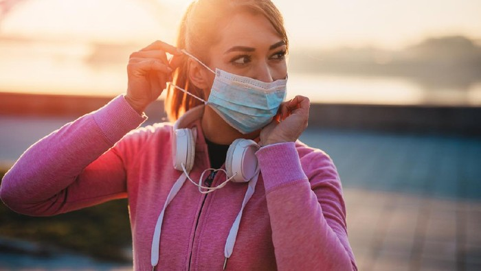 Beautiful female jogger putting protective mask on her face to protect herself from virus or allergy infection. Sunset in background.