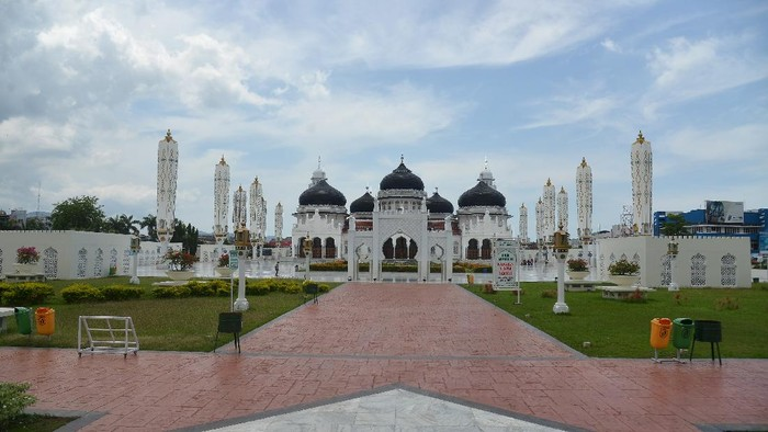 Seorang warga berjalan di halaman Masjid Raya Baiturrahman, Banda Aceh, Minggu (5/4/2020). Objek wisata religi Masjid Raya Baiturrahman yang juga merupakan salah situs sejarah itu sepi pengunjung pada hari libur dampak dari pandemi Corona Virus (COVID-19). ANTARA FOTO/Ampelsa/foc.