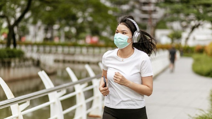 a asian woman doing a exercise in a park of Jakarta City, Indonesia, during quarantine cause corona pandemic