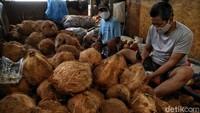 Pedagang mengupas kelapa untuk diolah menjadi santan.