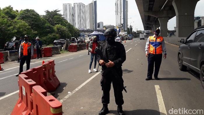 Seorang anggota Brimob bersenjata laras panjang disiagakan di check point gerbang tol (GT) Cikarang Barat untuk membantu mencegah keluarnya pemudik dari Jakarta di masa pembatasan sosial berskala besar (PSBB).