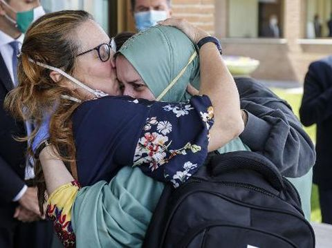 Italian volunteer aid worker Silvia Costanza Romano (R), who was kidnapped in Kenya in late 2018, wearing a khimar and face mask, embraces her mother Francesca upon her arrival at Romes military Ciampino airport on May 11, 2020, following her release. - Silvia Romano was 23 and working as a volunteer in the orphanage in Chakama village in southeast Kenya when she was seized by gunmen in November 2018. (Photo by FABIO FRUSTACI / ANSA / AFP) / Italy OUT / ITALY OUT