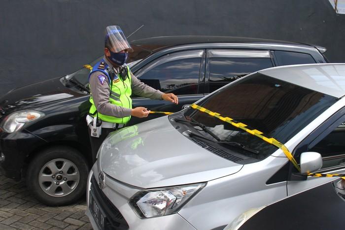 Polisi memasang garis polisi pada mobil travel ilegal yang ditahan di pos pemeriksaan Pembatasan Sosial Berskala besar (PSBB) Balearjosari, Malang, Jawa Timur, Jumat (22/5/2020). Sebanyak empat unit mobil travel ilegal yang mengangkut penumpang dari Madura dan Surabaya tersebut ditahan karena melanggar larangan mudik dari pemerintah saat PSBB sedang dilaksanakan di kawasan Malang Raya sebagai upaya pencegahan penyebaran COVID-19. ANTARA FOTO/Ari Bowo Sucipto/pras.
