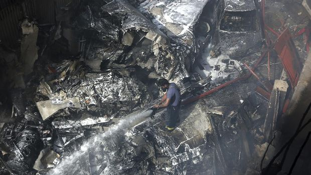 A firefighter tries to put out fire caused by plane crash in Karachi, Pakistan, Friday, May 22, 2020. An aviation official says a passenger plane belonging to state-run Pakistan International Airlines carrying more than 100 passengers and crew has crashed near the southern port city of Karachi. There were no immediate reports on the number of casualties. (AP Photo/Fareed Khan)