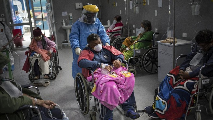 A doctor pushes a COVID-19 patient in a wheelchair in the emergency area of the Guillermo Almenara hospital in Lima, Peru, Friday, May 22, 2020. Despite strict measures to control the virus, this South American nation of 32 million has become one of the countries worst hit by the disease. (AP Photo/Rodrigo Abd)