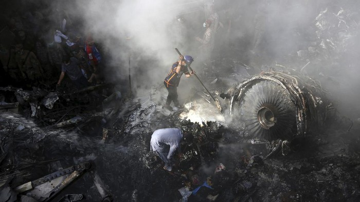 CORRECTS NUMBER OF PASSENGERS TO NEARLY 100, INSTEAD OF MORE THAN 100 - Volunteers look for survivors of a plane that crashed in a residential area of Karachi, Pakistan, May 22, 2020. An aviation official says a passenger plane belonging to state-run Pakistan International Airlines carrying nearly 100 passengers and crew crashed near Karachis airport. (AP Photo/Fareed Khan)