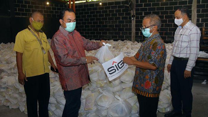 Kepala Departemen CSR SIG, Edy Saraya (kedua dari kiri) menyerahkan paket bantuan kebutuhan pokok kepada tokoh masyarakat, H. Khilmi (kedua dari kanan) di Gresik, Jawa Timur.