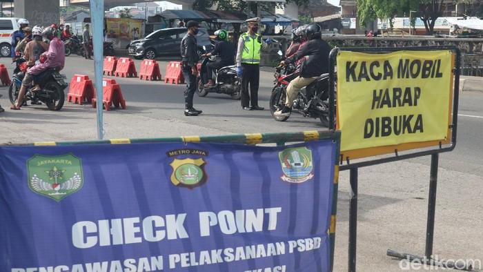 Petugas gabungan melakukan pengecekan pengendara di cek point PSBB, Sumber Artha, Kota Bekasi, Jawa Barat, Sabtu (23/5/2020).