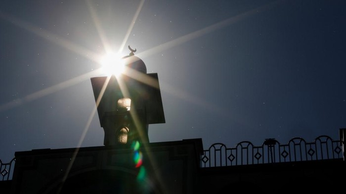 The sun shines behind the Omar Mosque in Berlins Kreuzberg district just hours before the start of the Muslim holy fasting month of Ramadan on April 23, 2020. (Photo by David GANNON / AFP)