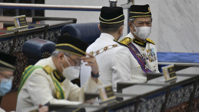 In this photo released by Malaysias Department of Information, Malaysias Prime Minister Muhyiddin Yassin, right, wearing a face mask along with his cabinet members attend the opening ceremony of the third term of the 14th parliamentary session at parliament house in Kuala Lumpur Monday, May 18, 2020.  Malaysias parliament held an unusual half-day sitting Monday, that was kept short due to the COVID-19 pandemic and saw Prime Minister Muhyiddin Yassin dodge a vote of no-confidence against him over two months since he came into power. (Nazri Rapai/Malaysias Department of Information via AP)