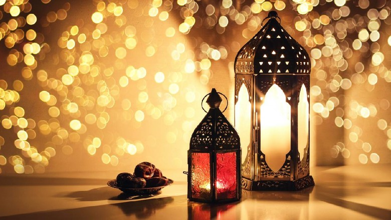 Ornamental Arabic lanterns with burning candles. Glittering golden bokeh lights. Plate with date fruit on the table. Greeting card for Muslim holiday Ramadan Kareem, iftar dinner background.