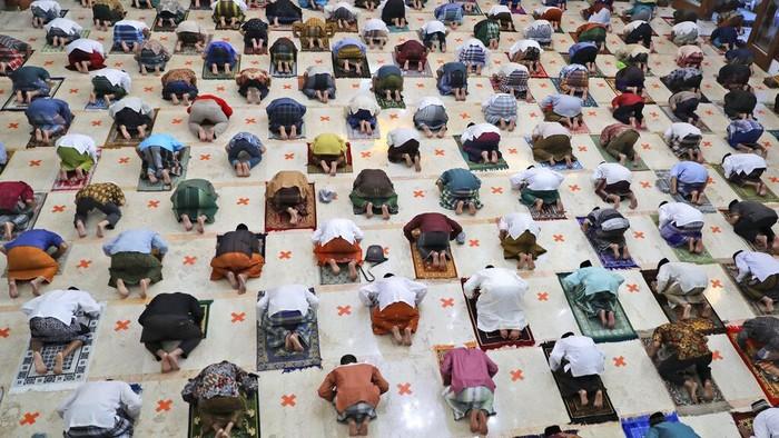 Umat Muslim Indonesia menjalani salat idul fitri dengan jarak terpisah guna memutus mata rantai penyebaran virus Corona. Salat Id digelar sebagai tanda Idul Fitri yang menandai akhir bulan puasa Ramadhan di Sidoarjo, Jawa Timur, Indonesia, Minggu, 24 Mei 2020. Jutaan orang di negara Muslim terbesar di dunia ini menandai festival keagamaan Idul Fitri yang diredam dan suram, akhir bulan puasa Ramadhan - perayaan tiga hari yang biasanya menggembirakan yang telah secara signifikan dikurangi karena kasus Coronavirus di Jawa Timur ini terus melambung tinggi angka kasus positifnya. (Foto AP / Trisnadi)