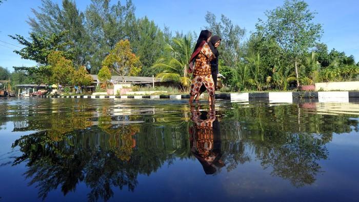 Warga melintas di jalan yang terendam banjir rob di Tiram Ulakan, Kabupaten Padangpariaman, Sumatera Barat, Senin (25/5/2020). Banjir rob akibat pasang air laut itu menggenangi kawasan tersebut sejak dua hari terakhir, mengakibatkan sejumlah rumah warga terendam. ANTARA FOTO/Iggoy el Fitra/wsj.