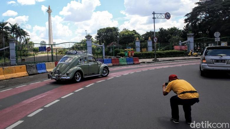 Pengunjung berfoto Dari balik Pagar Monumen Nasional, Jakarta, Senin (25/5/2020). PSBB Corona membuat tempat wisata ditutup untuk umum.