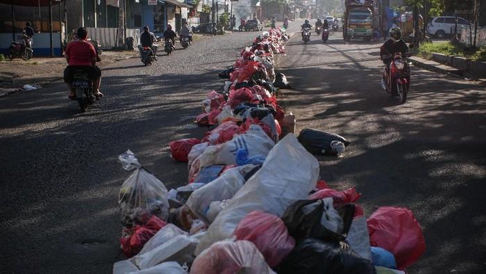 Pengendara melintas di dekat sampah yang menumpuk di pembatas jalan di Ciledug, Tangerang, Banten, Senin (25/5/2020). Wilayah tersebut sempat dipenuhi sampah rumah tangga yang tidak terurus karena libur lebaran. ANTARA FOTO/Rivan Awal Lingga/wsj.