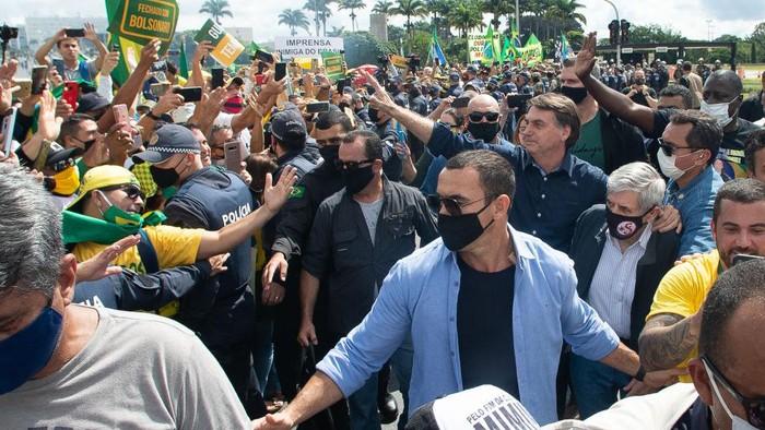 Presiden Brasil Jair Bolsonaro ikut turun ke jalan dan berbicara di hadapan para pendukungnya. Dia menyapa pendukungnya dengan tidak memakai masker.