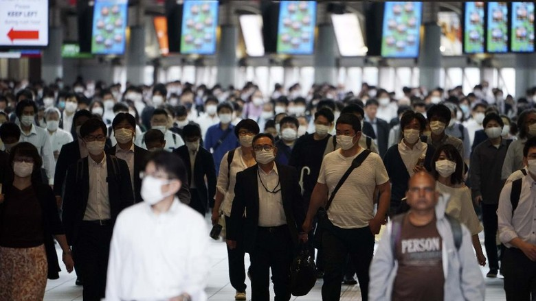 A station passageway is crowded with commuters wearing face mask during a rush hour Tuesday, May 26, 2020, in Tokyo.  Japanese Prime Minister Shinzo Abe lifted a coronavirus state of emergency in Tokyo and four other remaining prefectures on Monday, May 25, ending the declaration that began nearly eight weeks ago.(AP Photo/Eugene Hoshiko)