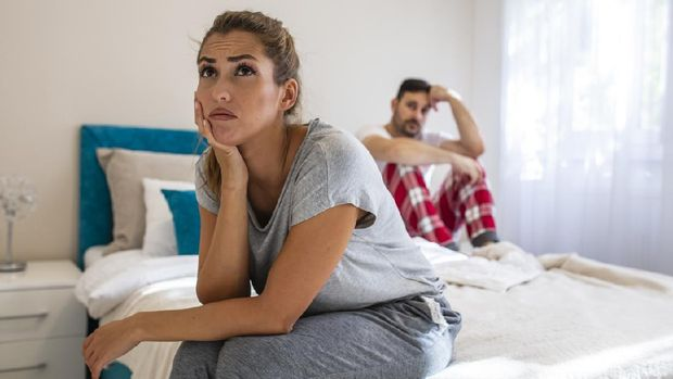 We have a problem. Young upset girl sitting on the edge of the bed, against her boyfriend, lying in bed. Frustrated sad girlfriend sit on bed think of relationship problems, thoughtful couple after quarrel lost in thoughts