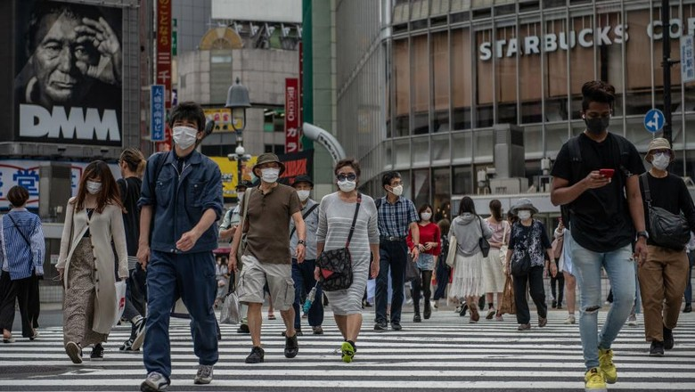 TOKYO, JAPAN - MAY 25: People, many wearing face masks, walk over Shibuya crossing on May 25, 2020 in Tokyo, Japan. As Covid-19 coronavirus cases in Japan continue to decline, Prime Minister Shinzo Abe today formally announced a complete end to the state of emergency that was imposed on April 7 in response to the outbreak. However, businesses around the country have been asked to implement social distancing and other protocols to avoid a second wave. To date, Japan has recorded 16,550 infections, 820 deaths and 13,413 recoveries from the virus. (Photo by Carl Court/Getty Images)