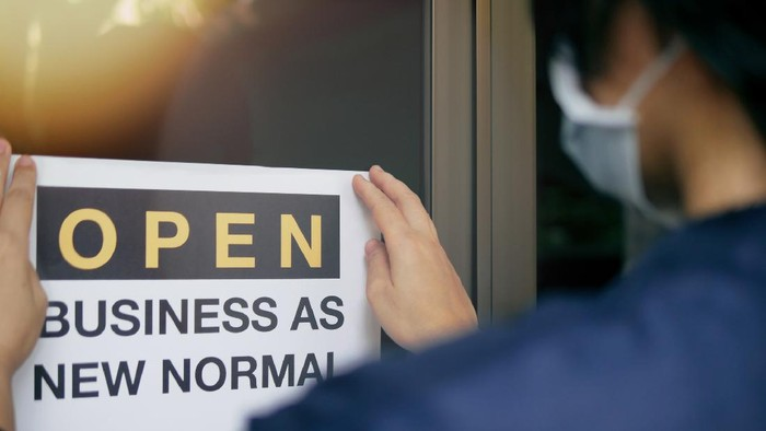 Reopening for business adapt to new normal in the novel Coronavirus COVID-19 pandemic. Rear view of business owner wearing medical mask placing open sign