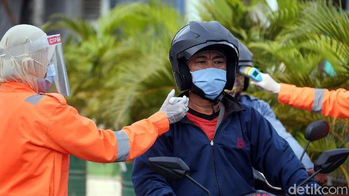 Petugas gabungan mengukur suhu tubuh para pengendara yang melintas di Jalan Raya Narogong KM16, Kota Bekasi. Ini bagian dari Operasi Ketupat Jaya 2020.