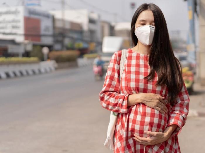 Ilustrasi wanita hamil pakai masker