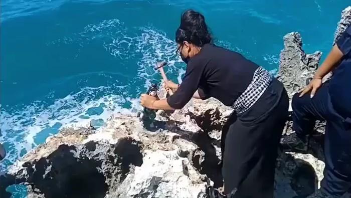 Pemasang melepas patung Nyi Roro Kidul yang terpasang di atas karang Pantai Waterblow Nusa Dua Bali (Screenshot video viral)