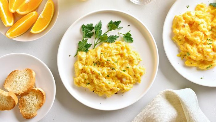 Natural light photo of farm fresh scrambled eggs on green glass plate with antique silver plated forkPlease view more rustic food images here: