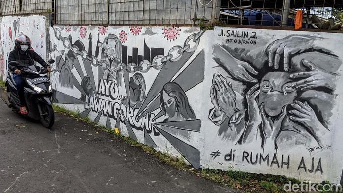 Warga melintas di depan mural perlawanan virus Corona, di Bintaro, Jakarta Selatan, Rabu (27/5). Mural ini mengajak warag hidup sehat untuk melawan virus Corona.
