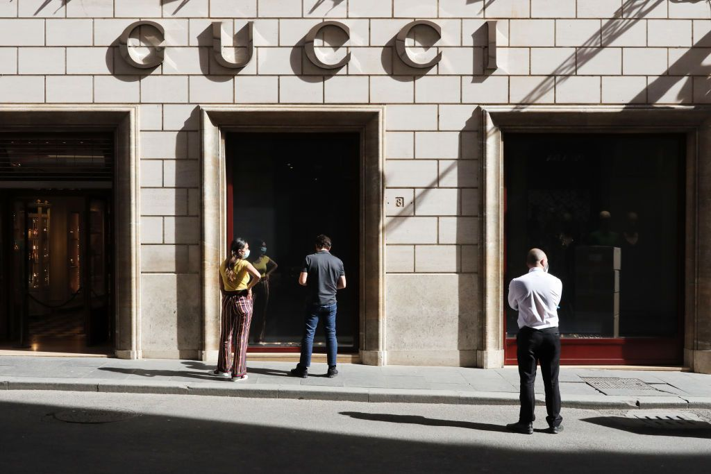 ROME, ITALY - MAY 15: Two Gucci employees decide how to separate the entrance and exit of customers in view of the reopening of the store on May 15, 2020 in Rome, Italy. Italy was the first country to impose a nationwide lockdown to stem the transmission of the Coronavirus (Covid-19) and it has started to ease these restrictions in recent weeks. The initial reopening date decided by the government would have been June 1, but due to pressure from the regional governments, trade associations and the public, this process has been accelerated. However, many businesses have complained that the government has not provided complete safety guidelines for the various types of businesses permitted to reopen and, consequently, some have decided to postpone their opening. (Photo by Marco Di Lauro/Getty Images)