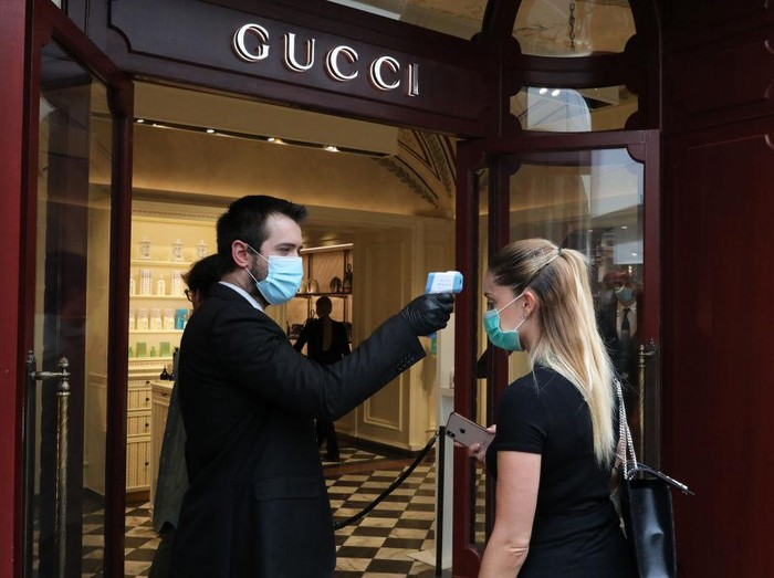 ROME, ITALY - MAY 18: A Gucci employee measures the temperature to a customer at the store entrance on May 18, 2020 in Rome, Italy. Museums, restaurants, bars, cafes, hairdressers and other shops have reopened, subject to social distancing measures, after more than two months of a nationwide lockdown meant to curb the spread of Covid-19. Churches are starting to celebrate Mass again, but there will be strict social distancing and worshippers must wear face masks. And citizens will no longer be required to justify their movements with self-certification. (Photo by Marco Di Lauro/Getty Images)