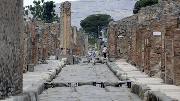People take photos as they visit the archeological site of Pompeii, Italy, as the site reopened to the public after a two-month lockdown due to the COVID-19 pandemic, Tuesday, May 26, 2020. (AP Photo/Alessandra Tarantino)