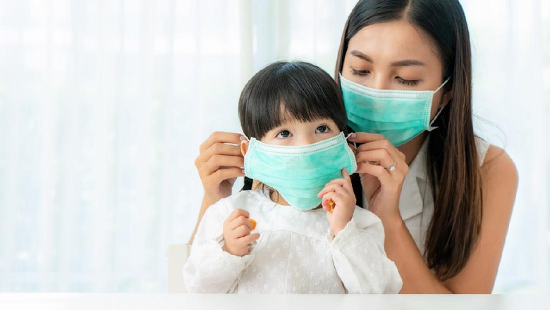 Stay at home quarantine coronavirus pandemic prevention.Mother and daughter in protective medical masks standing near on window and looks out window.