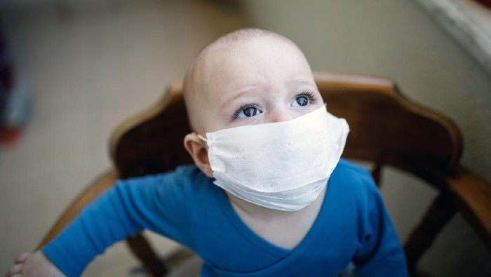 A little boy puts a medical mask on his face.