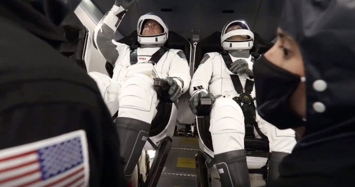 In this Wednesday, May 27, 2020 image from video made available by SpaceX, NASA astronauts Bob Behnken, background left, and Doug Hurley perform communication checks in the Crew Dragon capsule before launch from the Kennedy Space Center in Cape Canaveral, Fla. (SpaceX via AP)