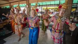 Penari menampilkan tarian tradisional Thailand dengan gunakan face shield. Meski lockdown dilonggarkan, Warga Thailand diimbau untuk patuhi protokol kesehatan.