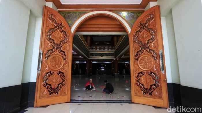 Pengurus membuat shaf sholat berjarak di Masjid Raya Agung Al Barkah, Kota Bekasi, Jawa Barat, Kamis (20/5/2020). Pemerintah Kota Bekasi mengizinkan masjid yang berada di kelurahan zona hijau untuk menggelar sholat Jumat berjamaah dengan protokol kesehatan. Antar jamaah dibuat berjarak 120 cm.