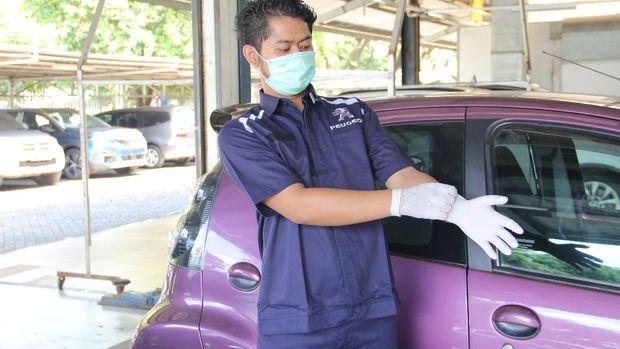 Mekanik Astra Peugeot menggunakan masker dan sarung tangan saat bekerja