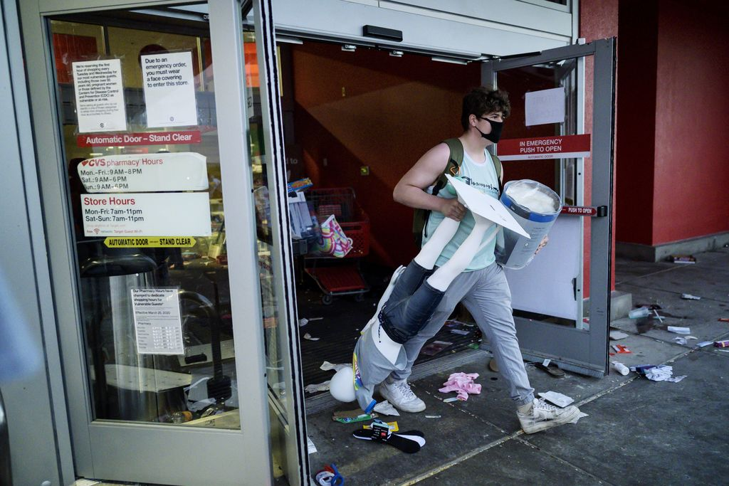 A man gets out of a Target store with merchandise, and a mannequin in Minneapolis on Wednesday, May 27, 2020. Violent protests over the death of a black man in police custody broke out in Minneapolis for a second straight night Wednesday, with protesters in a standoff with officers outside a police precinct and looting of nearby stores. (Aaron Lavinsky/Star Tribune via AP)