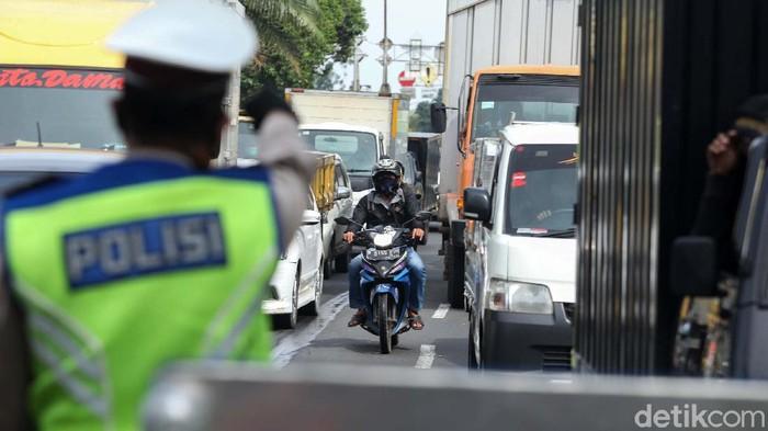 Petugas gabungan melakukan pengecekan terhadap warga dengan plat nomor luar Jakarta di Daan Mogot, Jakbar, Kamis (28/5). Pengecekan ini guna mencegah arus balik.