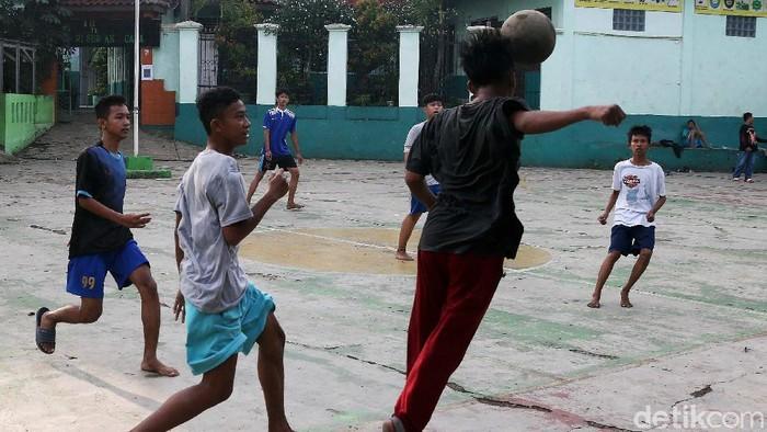 Sejumlah anak bermain bola di lapangan sekolah SMPN PGRI Surya Kencana, Cileungsi. Ngerinya mereka bermain tanpa memakai masker meski di tengah pandemi Corona.