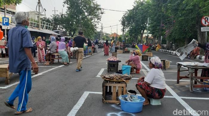 Sebuah pasar di Surabaya menerapkan physical  dan social distancing. Penerapan jaga jarak untuk lapak pedangang tertuang dalam aturan PSBB Surabaya jilid 3.