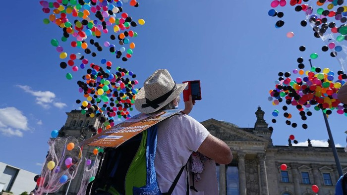 BERLIN, GERMANY - MAY 27: A protester wears a sign that reads: