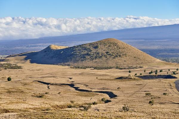 Erupsi gunung ini tidak meledak seperti letusan gunung strato atau maar karena memiliki tekanan gas yang rendah. Sementara itu lava cairnya berasal dari dapur magma yang dangkal dan magma yang juga cair. Contoh lain gunung api perisai adalah Gunung Mauna Loa di Hawaii. (Foto: Getty Images/Dhoxax)