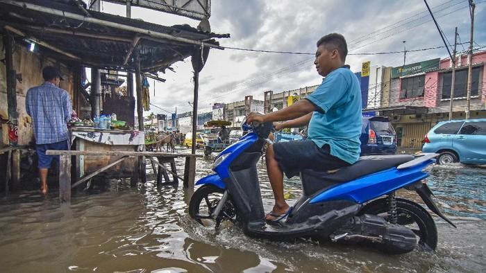 Seorang perempuan berjalan melintasi genangan air di jalan Pasar Kebon Roek, Ampenan, Mataram, NTB, Jumat (29/5/2020). Banjir tersebut diakibatkan oleh buruknya drainase dan tingginya intensitas hujan yang terjadi di wilayah Ampenan dan sekitarnya. ANTARA FOTO/Ahmad Subaidi/pras.
