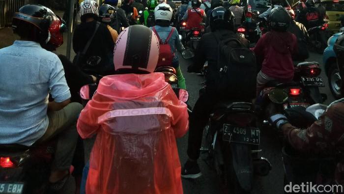 Warga berusaha melindungi dirinya agar tidak terpapar virus Corona. Pemotor ini bahkan rela memakai jas hujan sebagai APD untuk mencegah Corona.