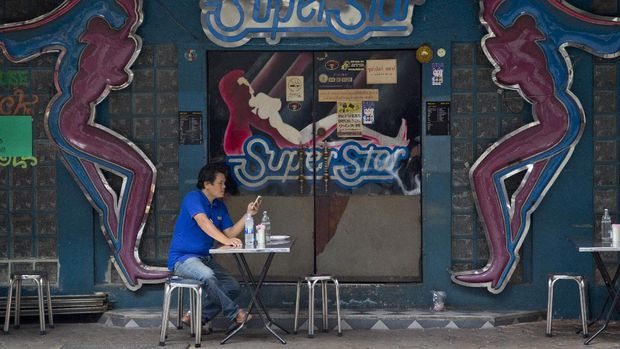 A man sitting outside an adult entertainment establishment in the Patpong nightlife area looks at his mobile phone after eating a meal in Bangkok, Thailand, Thursday, July 5, 2018. (AP Photo/Gemunu Amarasinghe)